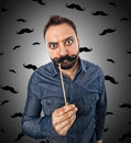 Young man with photo booth shaped mustache and background small mustaches Royalty Free Stock Photo