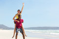 Young man piggybacking girlfriend at the beach portrait of african men carrying on his back Royalty Free Stock Photos