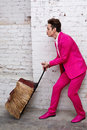 Young man in pink suit pulls roller bag with hairy sides Royalty Free Stock Photo