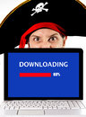 Young man in pirate costume with computer laptop downloading files copyright violation and representing illegal downloads movies Stock Photos