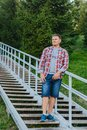 A young man in a plaid shirt and denim shorts stands on a metal Royalty Free Stock Photo