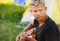 Young man plaing by guitar in the forast camp Royalty Free Stock Photography