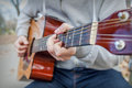 Young man playing acoustic guitar close up outdoors in autumn park Royalty Free Stock Photo