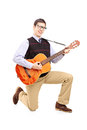 Young man playing an acoustic guitar and kneeling isolated on white background Stock Photos