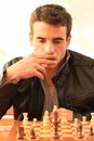 Young man playing chess in black leather jacket thinking while wooden Royalty Free Stock Photo