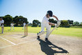 Young man playing cricket at field against clear sky Royalty Free Stock Photo