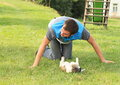 Young man playing with a dog in t shirt stripes puppy on green grass slide behind Stock Images