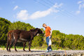 Young man playing and feed wild donkeys, Cyprus, Karpaz National Park Wild Donkey Protection Area. Royalty Free Stock Photo