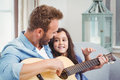 Young man playing guitar with daughter Royalty Free Stock Photo