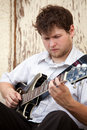 Young man playing guitar outdoors Royalty Free Stock Image