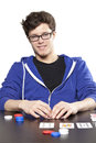Young man playing poker at table Stock Image