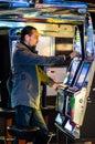 Young Man Playing At Slot Mach...