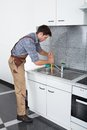 Young man with plunger handsome using in kitchen sink Royalty Free Stock Image