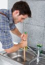 Young man with plunger handsome using in kitchen sink Stock Image