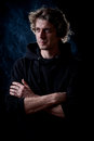Young man portrait curly hair caucasian wearing black hooded sweatshirt low key taken on black background full of smoke Royalty Free Stock Image