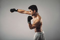 Young man practicing shadowboxing on grey background profile view of muscular male model working out Royalty Free Stock Photo