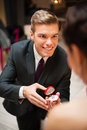 Young man proposing to his pretty girlfriend men romantically and offering engagement ring Royalty Free Stock Photography