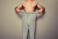 Young man pulling at his trousers a is Royalty Free Stock Photo