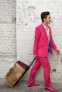 Young man pulls hairy roller bag in pink suit Royalty Free Stock Image