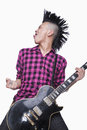 Young man with punk Mohawk playing guitar Royalty Free Stock Photo
