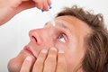 Young man putting eye drops Royalty Free Stock Photo