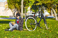 Young man reading a book in autumn park standing next to his bicycle Stock Photography