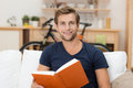 Young man reading a book handsome sitting on sofa at home hardcover enjoying the story or studying towards his university Royalty Free Stock Image