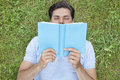 Young man reading book while lying on grass Royalty Free Stock Photo