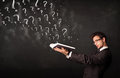 Young man reading a book with question marks coming out from it confused Stock Photography