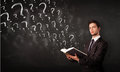Young man reading a book with question marks coming out from it confused Royalty Free Stock Images