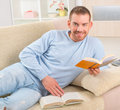 Young man reading book smiling handsome storybooks on couch at home Royalty Free Stock Photo