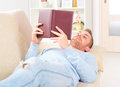Young man reading book smiling handsome storybooks on couch at home Royalty Free Stock Image
