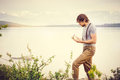 Young Man reading book and writing notes outdoor Royalty Free Stock Photo