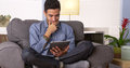 Young man reading an e book on his tablet Royalty Free Stock Photo