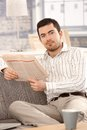 Young man reading news sitting on sofa smiling newspaper at home Stock Images