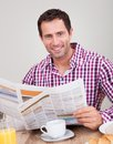 Young Man Reading Newspaper At Breakfast Stock Images