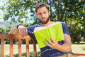 Young man reading on park bench Royalty Free Stock Photo