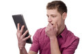 Young man reading a shocking news on the tablet. Royalty Free Stock Images