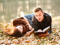 Young man reading to his girlfriend men lying down near lake Stock Photography