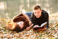 Young man reading to his girlfriend men lying down near lake Royalty Free Stock Photo