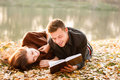 Young man reading to his girlfriend men lying down near lake book Royalty Free Stock Images