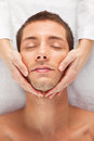 Young man receiving facial massage Stock Image