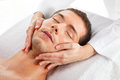 Young man receiving facial massage Stock Photos