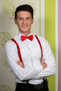 A young man with a red bow and suspenders posing on colorful background. Royalty Free Stock Photo