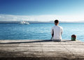 Young man relax siting on pier Royalty Free Stock Image