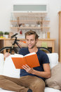 Young man relaxing reading a book casual unshaven handsome at home on sofa in the living room or studying Stock Photos