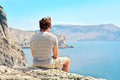 Young man relaxing on rocky cliff sitting and looking on sea mountains summer time freedom concept Stock Image