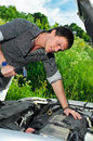 Young man repairing broken car Stock Images