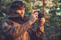 Young man with retro photo camera outdoor hipster lifestyle forest nature on background Royalty Free Stock Photography