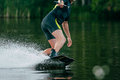 Young man rides a wakeboard on lake in summer around him water splashes Royalty Free Stock Photo